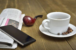A wooden table with newspaper, smart phone, tobacco pipe and a cup of coffee. Stock Image