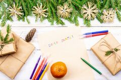 On the wooden table are an old yellow paper that says, Dear Santa Claus red, pencils, pens assorted colors gift and tree