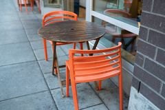 Wooden table with orange chairs royalty free stock photography
