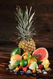 Pineapple, vivid grapefruit, pears, strawberries, leaves of mint, blueberries, lime and ice on a wooden brown background stock photos