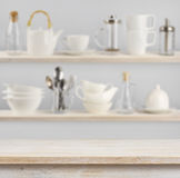 Wooden table over background of shelves with kitchen utensils Stock Photography