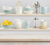 Wooden table over background of shelves with kitchenware Royalty Free Stock Photography
