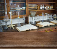Wooden table over defocused vintage chemical laboratory background Stock Photos
