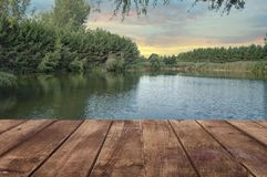 Wooden table perspective and a river landscape in background. royalty free stock photos
