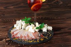 A glass of fruit beverage with a slice of orange, a plate of Roquefort and ham on a wooden background. Royalty Free Stock Photography
