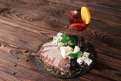 A glass of fruit beverage with a slice of orange, a plate of Roquefort and ham on a wooden background. Royalty Free Stock Image