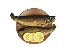 On the wooden table is a plate with two baked fish Royalty Free Stock Photo