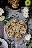 On a wooden table on a platter, apples are baked in the form of roses. The table is decorated with cotton napkins, fresh apples an royalty free stock image