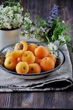 On a wooden table on a platter of fresh apricots with bones, decorated with flowers Stock Photo