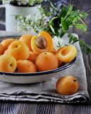 On a wooden table on a platter of fresh apricots with bones, decorated with flowers Stock Photos