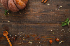 Wooden table with pumpkin and spices flat lay. Top view on rustic workplace with ingredients for preparing squash meal, free space. Kitchen, recipe, cooking Royalty Free Stock Photography