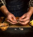 Male hands brushing garlic on a black wooden table. Rustic lifestyle royalty free stock image