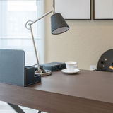 Wooden table with reading lamp and tea cup in modern working room Stock Photos