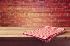 Wooden table with red checked tablecloth over brick wall Stock Images