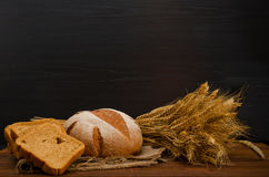 Wooden table with round and square rye bread, a sheaf, a black background Stock Photo