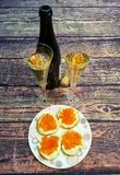 on wooden table sandwiches from baguette with red caviar on a plate and glasses of champagne and a bottle of champagne Royalty Free Stock Photos