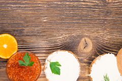 On a wooden table sandwiches with butter and fish caviar royalty free stock images