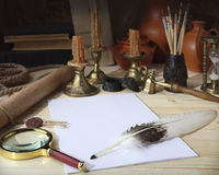 On the wooden table are: a scroll with a seal, sheets of white paper, a goose feather, an inkwell, tassels, a magnifying glass, b. On the wooden table are: a stock images