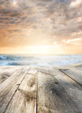 Wooden table at sea. Wooden table and sunset at seaside. Focus on table, blurred background Stock Photo