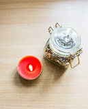 On a wooden table separately worth the red candle. `Wine` tablet with an inscription. Jar with flax seeds on a beige wooden table. The composition of red Stock Image