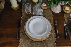 Wooden table set with candles, white plate and gray napkin stock images
