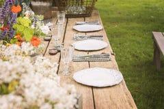 Garden dinner party. Wooden table setup for garden party or dinner reception Stock Photos