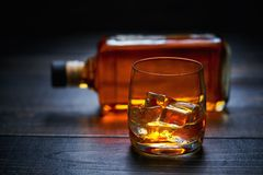 Whiskey with ice  cube on a wooden table Royalty Free Stock Photography