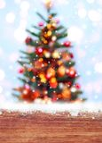 Wooden table with snow place and Christmas tree background with blurred, sparking, glowing. Royalty Free Stock Photo