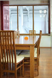 Wooden table, some chairs and window. Royalty Free Stock Image