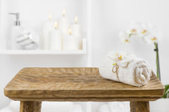 Wooden table with spa towel on blurred bathroom shelf background stock images