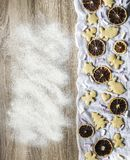 Wooden table is sprinkled with flour ginger spice cakes. A wooden table is sprinkled with flour, and ginger spice cakes are laid out on the white cloth on the Royalty Free Stock Images