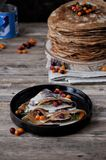 On a wooden table on a stand a pile of thin pancakes with condensed milk and berries.  royalty free stock photography