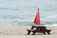 Wooden table 2. Wooden table stands alone on the beach on a cloudy summer day, next two unsolved red umbrella in the background Sea Stock Images