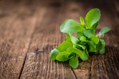 Wooden table with Stevia leaves (selective focus) Stock Photos
