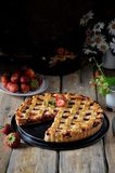 On a wooden table, strawberry pie in a cut stock image