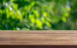 Wooden table surface and blurred leaves of a tree in the background stock image