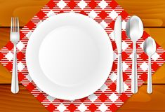 Wooden table, cloth, plate and stainless cutlery Royalty Free Stock Photos