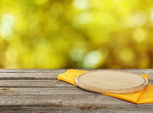 Wooden table with tablecloth and cutting board, close up. Wooden table with tablecloth and cutting board Stock Image