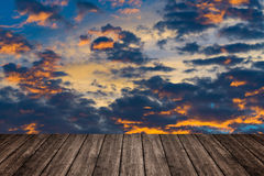 Wooden table or terrace on sunset sky and clouds, color and dark Stock Image
