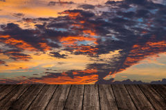 Wooden table or terrace on sunset sky and clouds, color and dark Royalty Free Stock Photos