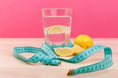 On the table tere is a glass with water and a slice of lemon, next to is a juicy lemon and a measuring tape. Stock Photos