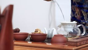 On the wooden table there is a set for the Chinese tea ceremony, cups, teapot and gaiwan.  stock video footage