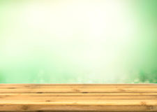 Wooden table top with abstract blur green stock photo