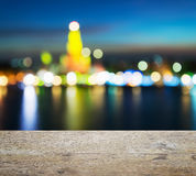 Wooden table top with abstract light bokeh of Wat Arun Ratchawararam Temple of Dawn Royalty Free Stock Photography