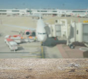 Wooden table top with blur of aircraft and loading area Stock Photos