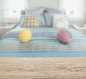 Wooden table top with blur of beddroom with decorative pillow on bed. Wooden table top with blur of bedroom with decorative pillow and football on bed Stock Photos