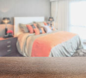 Wooden table top with blur of bedroom in lively style Stock Image