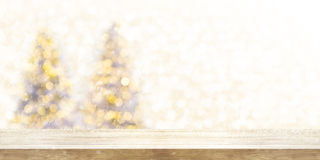 Wooden table top with blur Christmas tree background in snowfall. Panoramic banner. Can be used product display Stock Photos