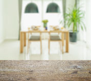 Wooden table top with blur of dining table and chairs Stock Images