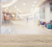 Wooden table top with blur image of shopping mall interior with bokeh. As background Royalty Free Stock Photo